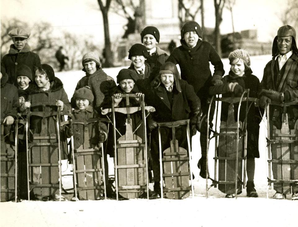 February 6, 1930: Winter provided splendid coasting on Boston Common and hundreds of youngsters turned out for sliding on the historic grounds. These coasters wait their turn for a slide on the toboggan chute.